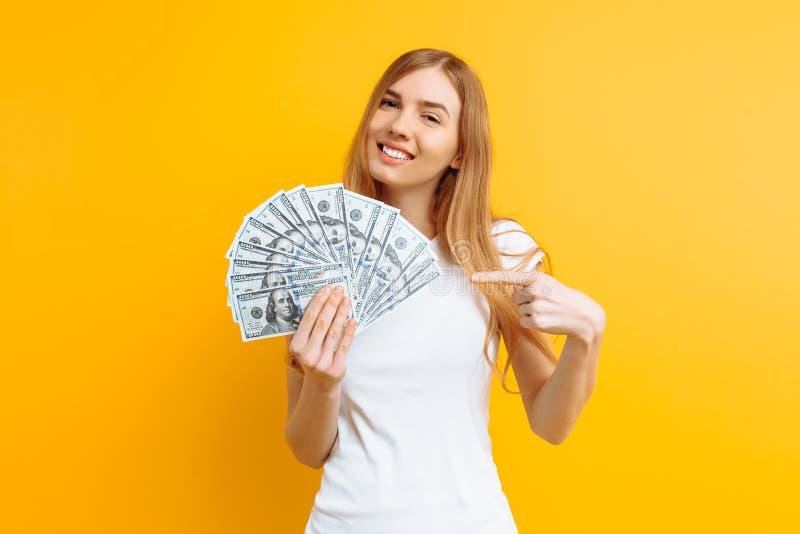 Ritratto di una ragazza contenta felice che tiene un mucchio delle banconote e che esamina la macchina fotografica su un fondo gi fotografia stock