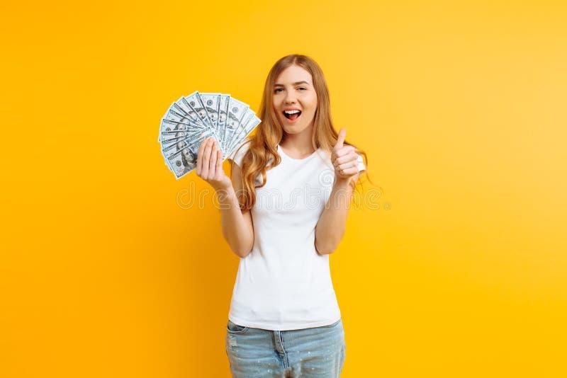Ritratto di una ragazza contenta felice che tiene un mucchio delle banconote e che esamina la macchina fotografica su un fondo gi immagini stock