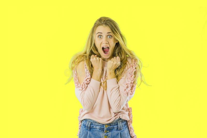 Ritratto di una ragazza contentissima che grida sopra il fondo giallo fotografia stock libera da diritti