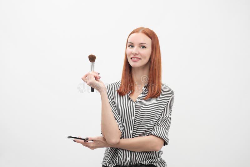 Ritratto di una ragazza dai capelli rossi, trucco dell'attore, professionale su fondo bianco I pennelli e la tavolozza a disposiz immagine stock libera da diritti