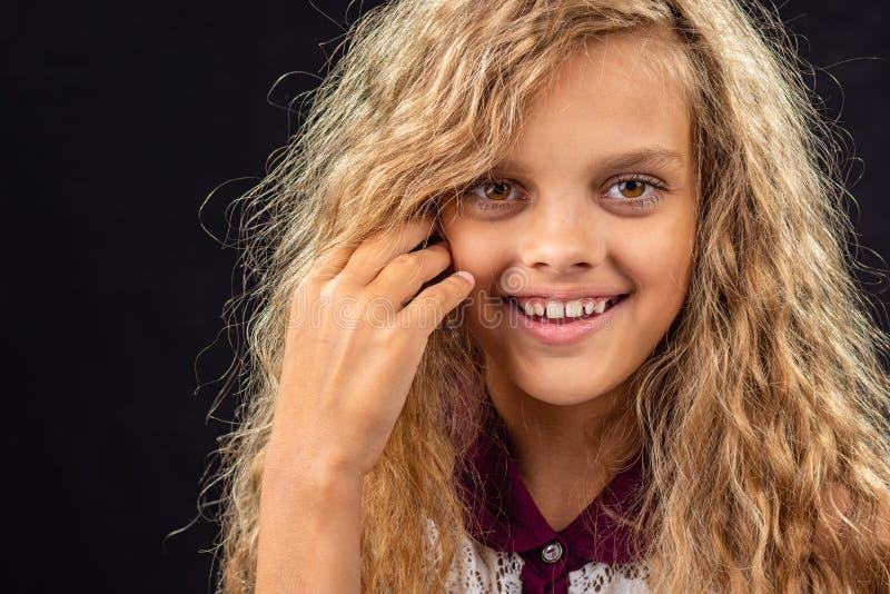 Ritratto di una ragazza di dieci anni che sorride ampiamente con i capelli biondi ricci immagini stock libere da diritti