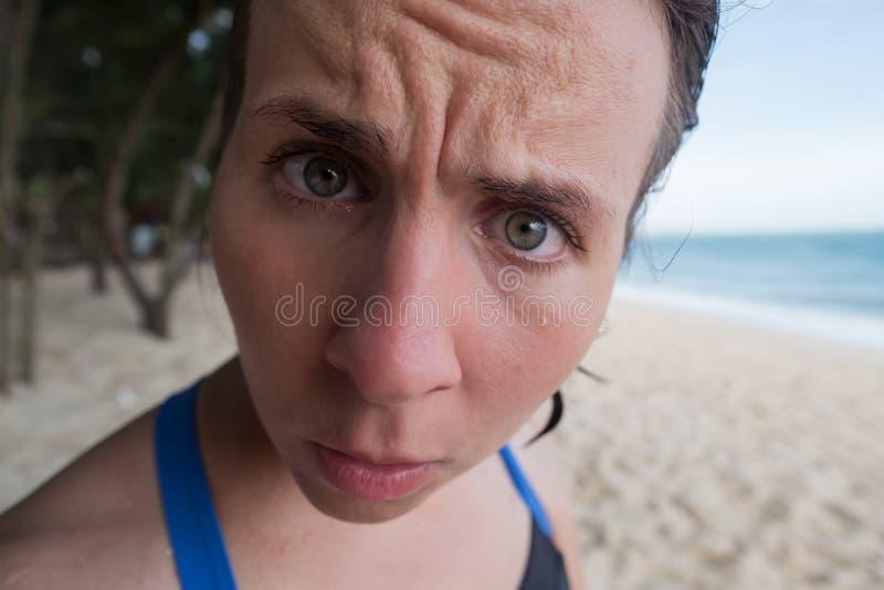 Ritratto di una ragazza divertente Ha capelli bagnati dopo il bagno ed esamina la macchina fotografica nella sorpresa immagine stock libera da diritti