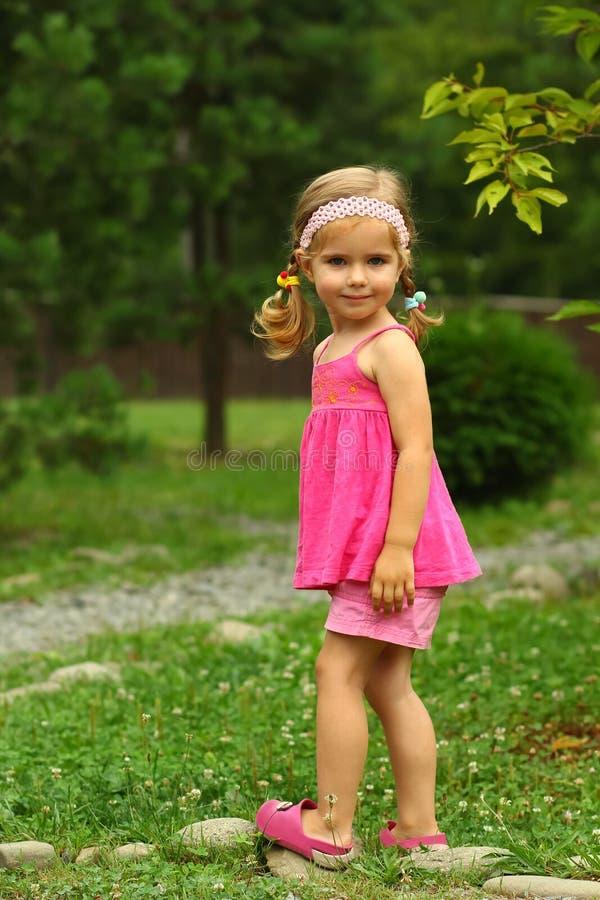 Ritratto di una ragazza di due anni sveglia del bambino nel rosa, equilibrante sulle rocce in parco immagine stock