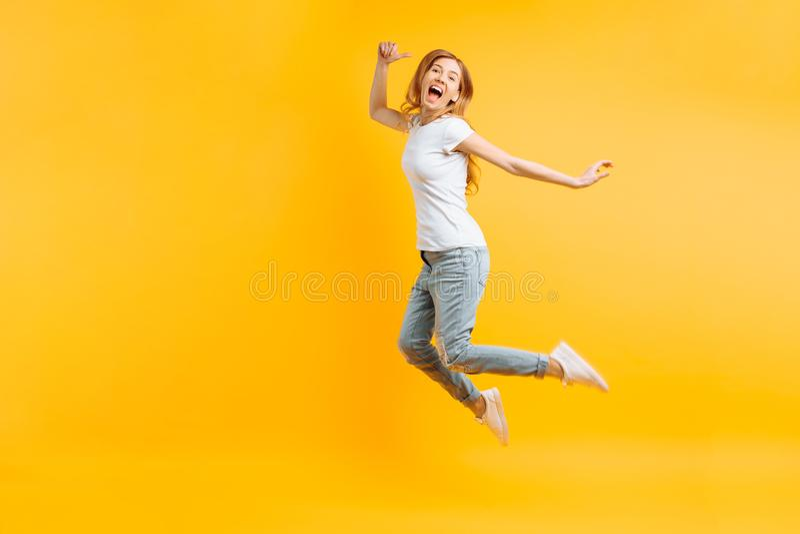 Ritratto di una ragazza entusiasta allegra in una maglietta bianca che salta per la gioia su un fondo giallo immagini stock libere da diritti