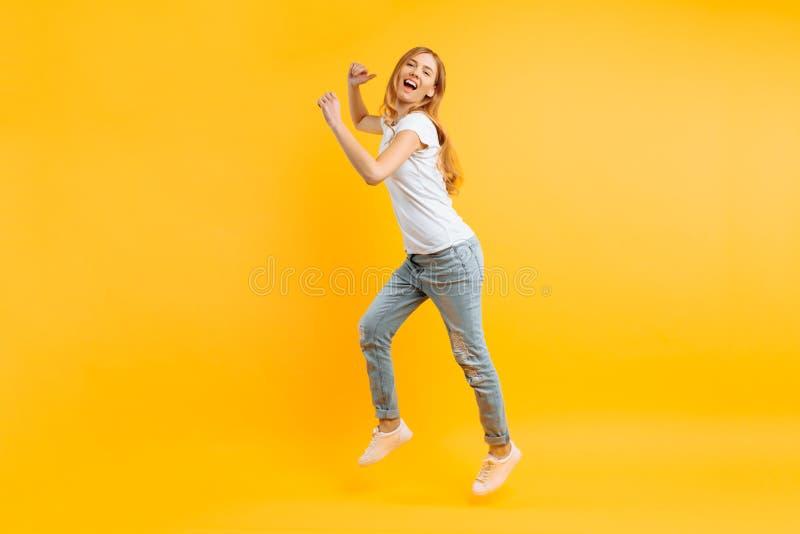 Ritratto di una ragazza entusiasta allegra in una maglietta bianca che salta per la gioia su un fondo giallo fotografie stock libere da diritti