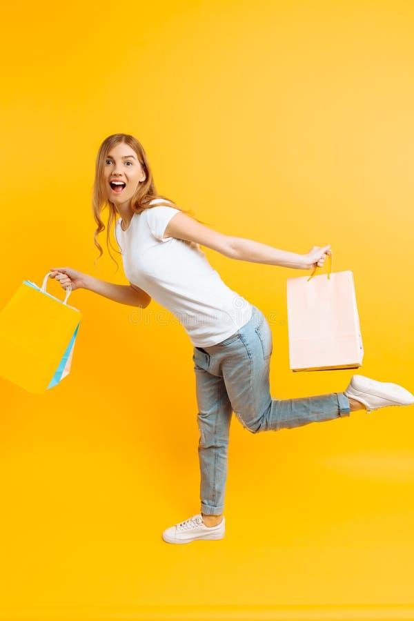 Ritratto di una ragazza entusiasta con le borse in mani, ragazza felice dopo la compera sul fondo giallo immagine stock