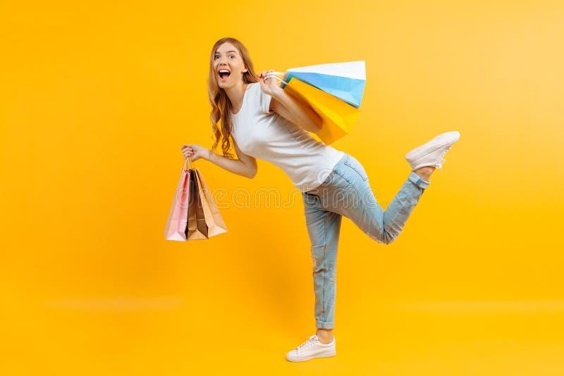Ritratto di una ragazza entusiasta con le borse in mani, ragazza felice dopo la compera sul fondo giallo immagini stock
