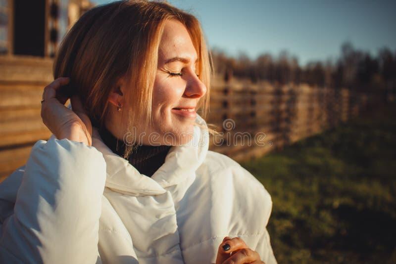 Ritratto di una ragazza felice con un sorriso soddisfatto e gli occhi chiusi Una donna in un rivestimento bianco, primo piano Il  fotografia stock libera da diritti