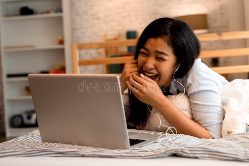 Ritratto di una ragazza felice dell'Asia in abiti casuali sdraiata sul letto mentre fa una videochiamata con un computer portatil fotografia stock