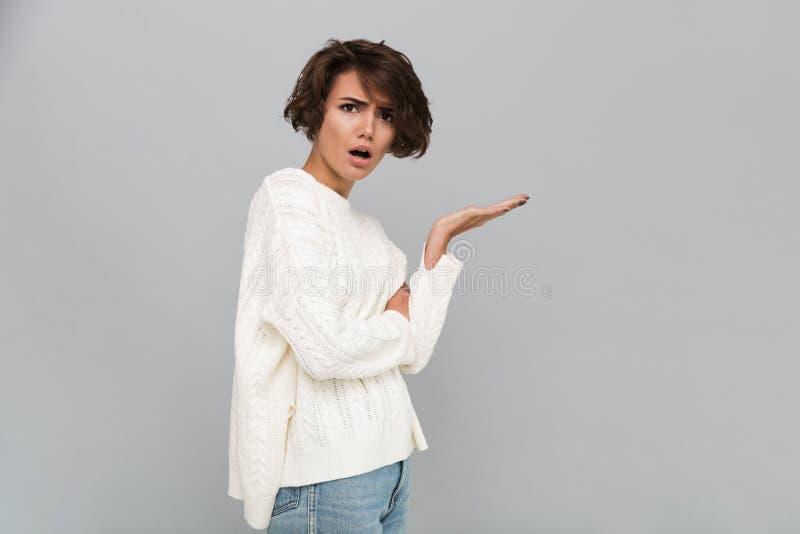 Ritratto di una ragazza frustrata confusa in maglione fotografia stock