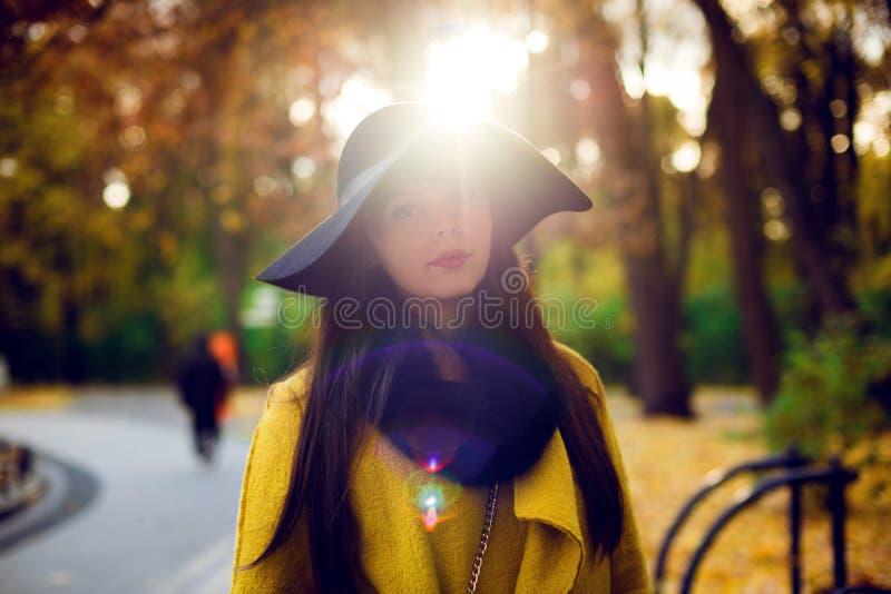 Ritratto di una ragazza nella camminata black hat in un parco di autunno fotografie stock