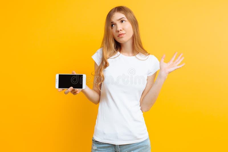 Ritratto di una ragazza pensierosa incerta che mostra uno schermo in bianco di un telefono cellulare su un fondo giallo fotografie stock libere da diritti