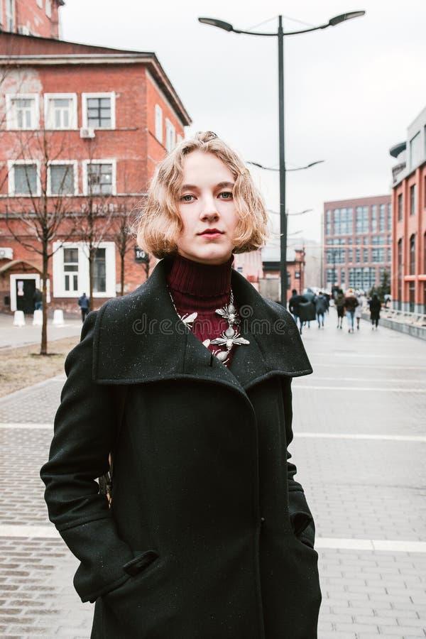 Ritratto di una ragazza riccia bionda che posa per la macchina fotografica immagine stock libera da diritti