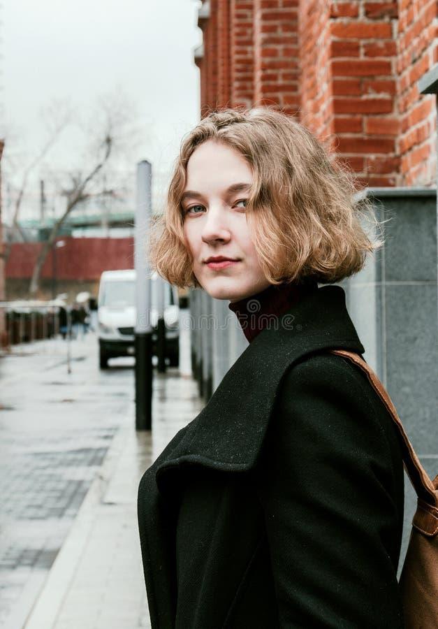Ritratto di una ragazza riccia bionda che posa per la macchina fotografica fotografia stock