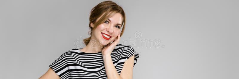 Ritratto di una ragazza smilling su un backgroud grigio Ragazza che tiene il suo fronte immagine stock libera da diritti