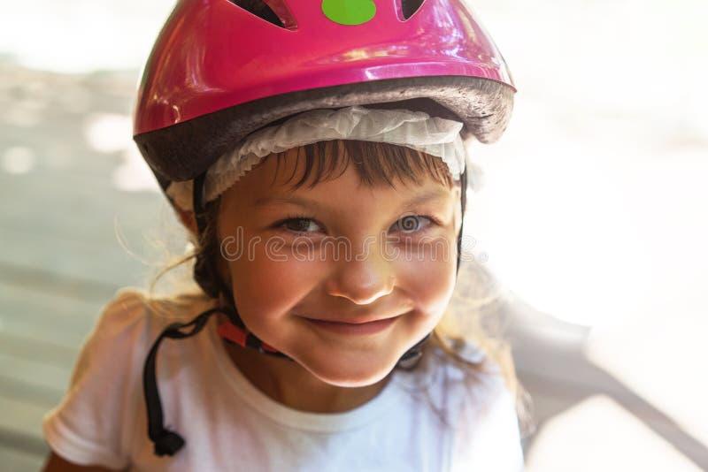 Ritratto di una ragazza sorridente 5 anni in un primo piano rosa del casco della bicicletta sulla via fotografia stock