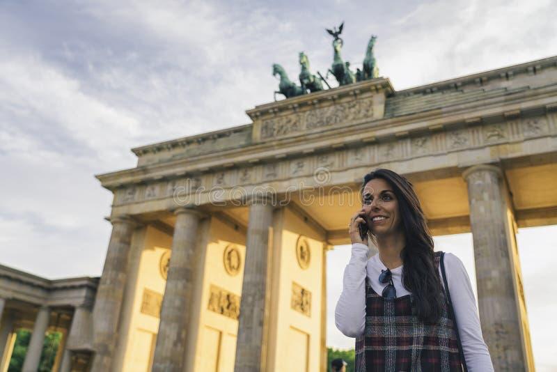 Ritratto di una ragazza sorridente che parla al cellulare contro Brandenburg Fate a Berlino, Germania fotografia stock libera da diritti