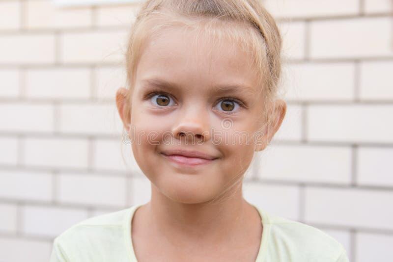 Ritratto di una ragazza sorridente sei anni contro fondo di un muro di mattoni fotografie stock libere da diritti