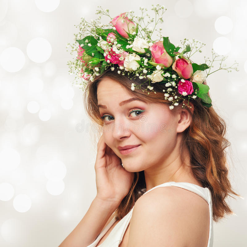 Ritratto di una ragazza sorridente sveglia in una corona delle rose fotografia stock
