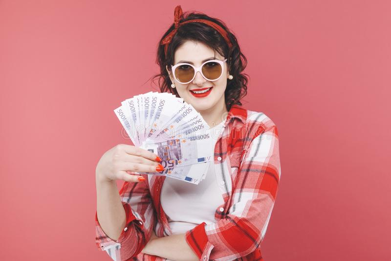 Ritratto di una ragazza sorridente, tenente mazzo di banconote dei soldi ed esaminante telefono cellulare isolato sopra il rosa fotografie stock