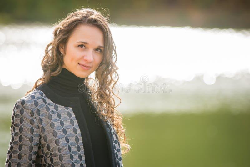 Ritratto di una ragazza su un fiume del cappotto di autunno del fondo immagini stock libere da diritti