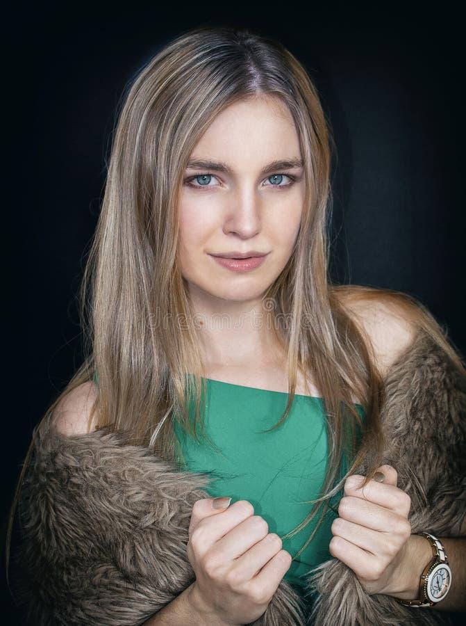 Ritratto di una ragazza, su un fondo nero Una bella bionda in un vestito verde e con pelliccia sulle sue spalle immagini stock libere da diritti