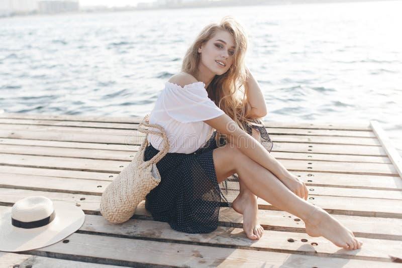Ritratto di una ragazza sveglia all'aperto nella seduta su un pilastro in primavera immagine stock