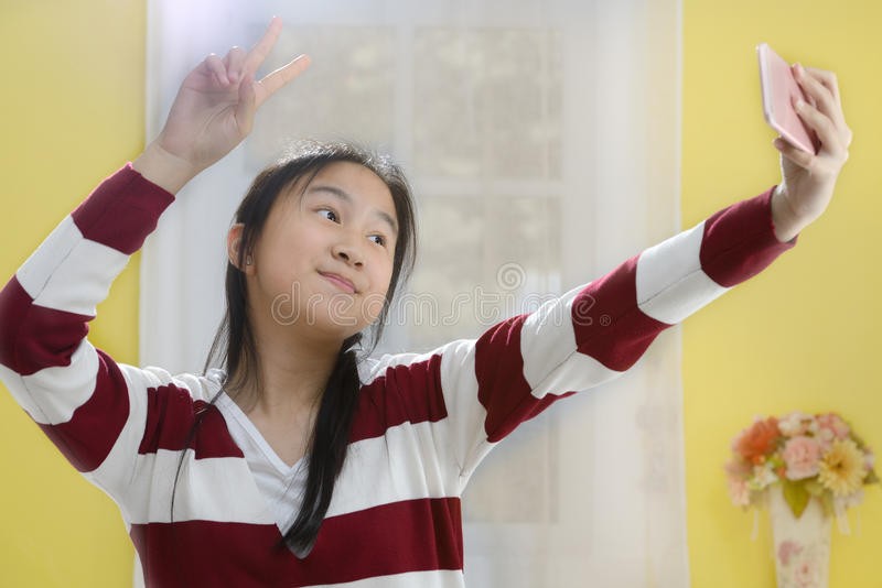 Ritratto di una ragazza sveglia sorridente che fa la foto del selfie immagine stock libera da diritti