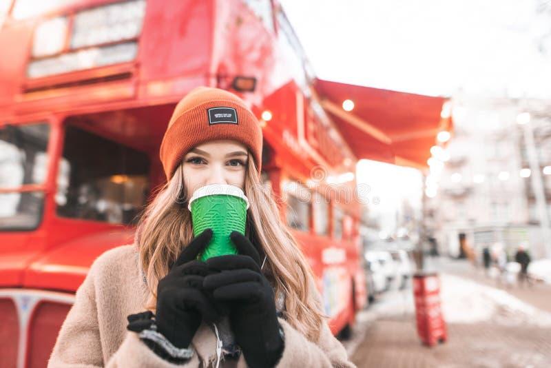 Ritratto di una ragazza sveglia sui vestiti caldi, stante sui precedenti di un caffè rosso del bus, caffè bevente da una tazza, g fotografia stock