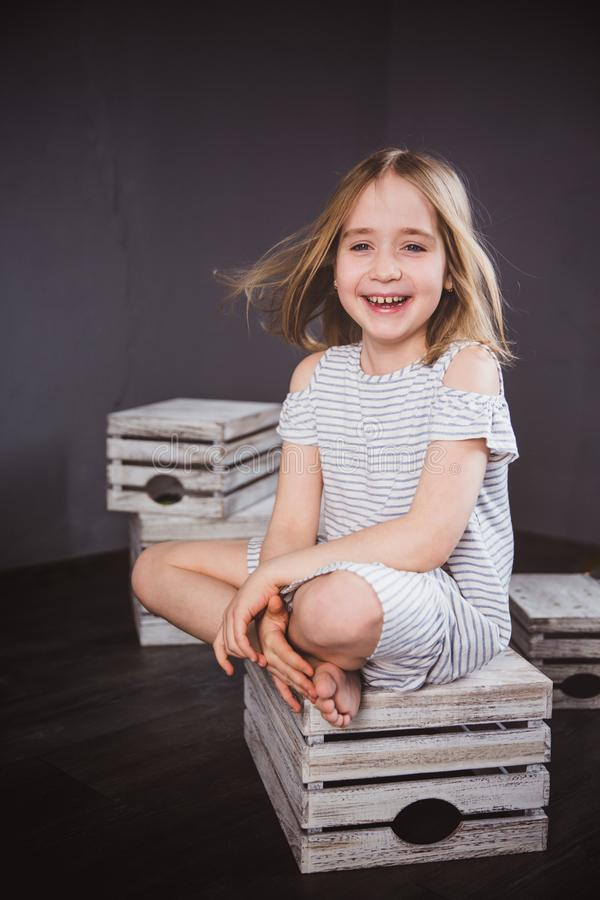 Ritratto di una ragazza teenager felice in vestito da estate in studio Si siede sulle scatole, il vento che soffia i suoi capelli fotografia stock libera da diritti