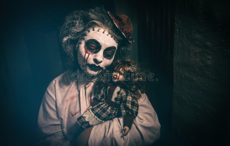 Ritratto di una ragazza terrificante con la bambola sanguinosa immagini stock
