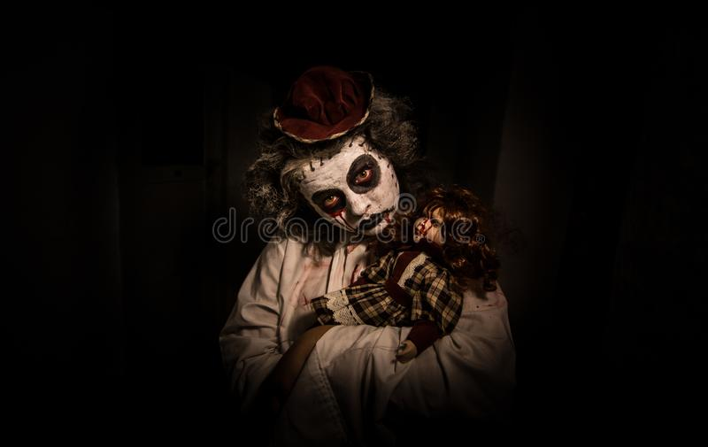 Ritratto di una ragazza terrificante con la bambola sanguinosa immagine stock