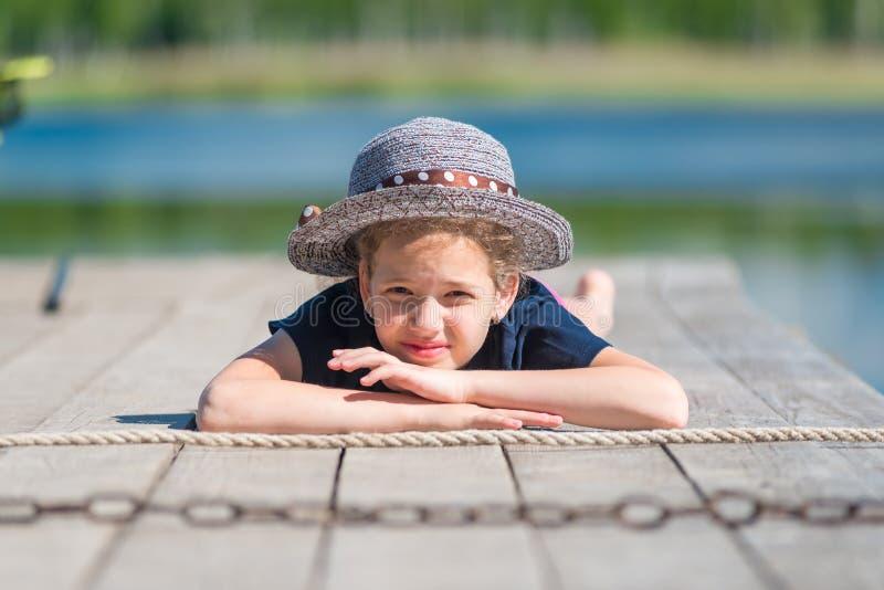 Ritratto di una ragazza in un cappello su un pilastro di legno fotografia stock libera da diritti