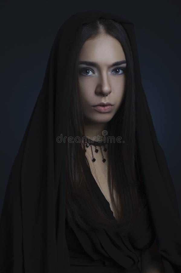 Ritratto di una ragazza in un vestito nero con la sua testa coperta immagini stock libere da diritti