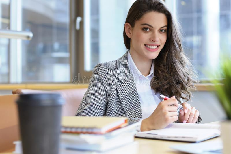 Ritratto di una studentessa graziosa con il computer portatile in biblioteca fotografia stock