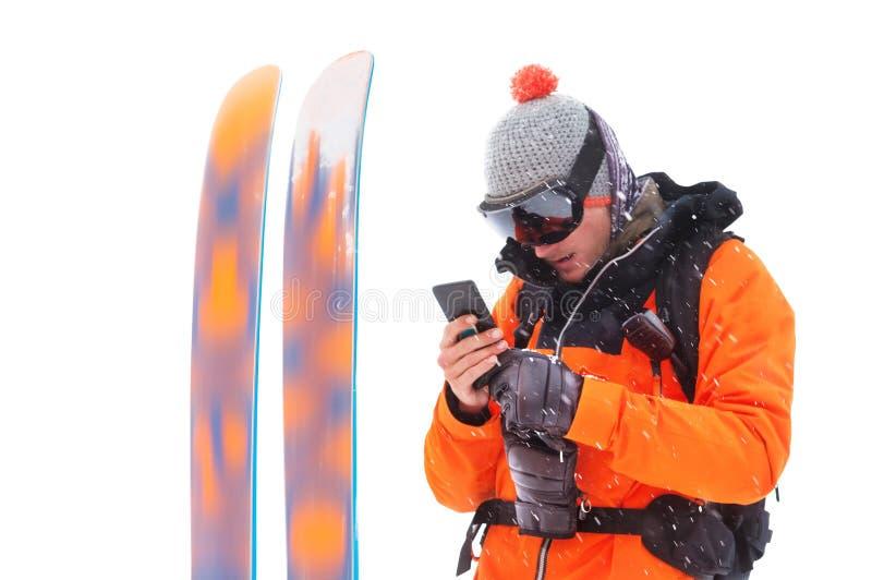 Ritratto di uno sciatore professionista dell'atleta con un telefono cellulare in sue mani accanto agli sci isolati su fondo bianc fotografia stock