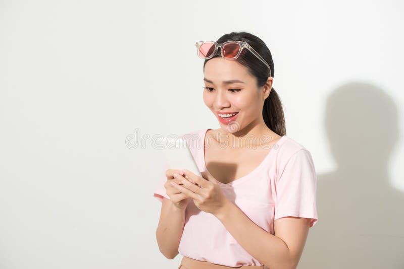 Ritratto di uno smartphone casuale sorridente della tenuta della donna sopra fondo bianco fotografie stock