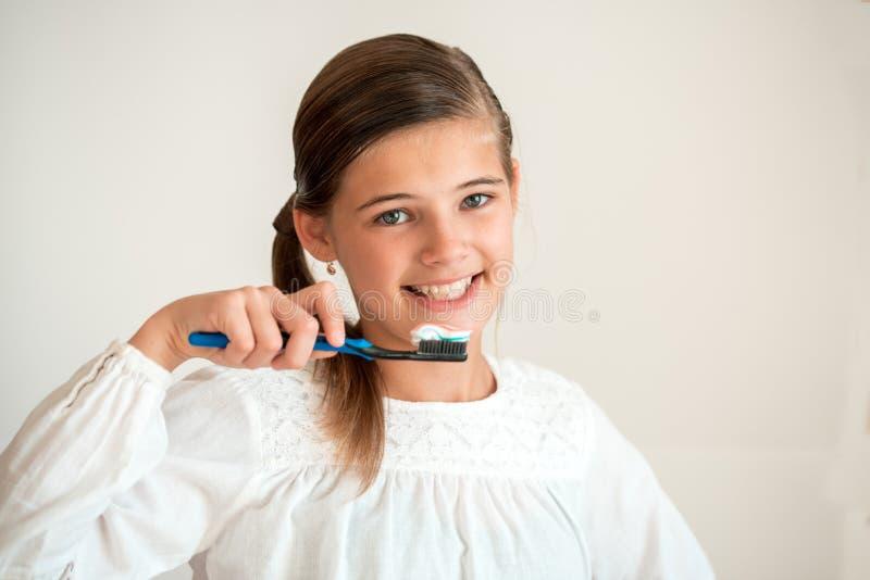 Ritratto di uno spazzolino da denti sveglio sorridente della tenuta della donna isolato su un fondo bianco fotografia stock