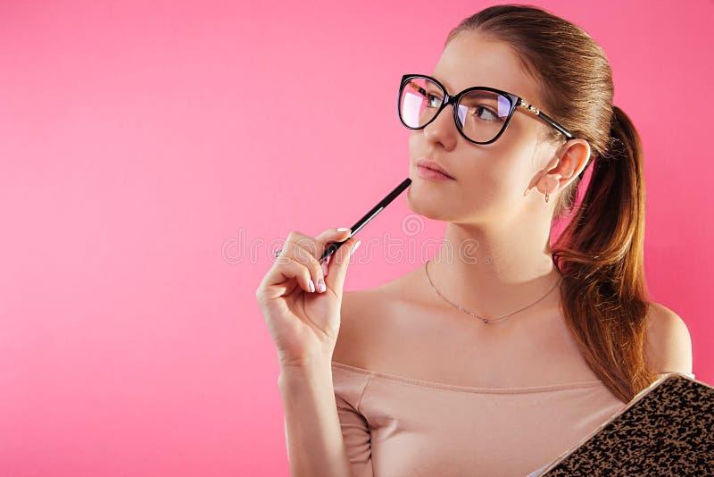 Ritratto di uno studente grazioso con i vetri d'uso di un quaderno fotografie stock
