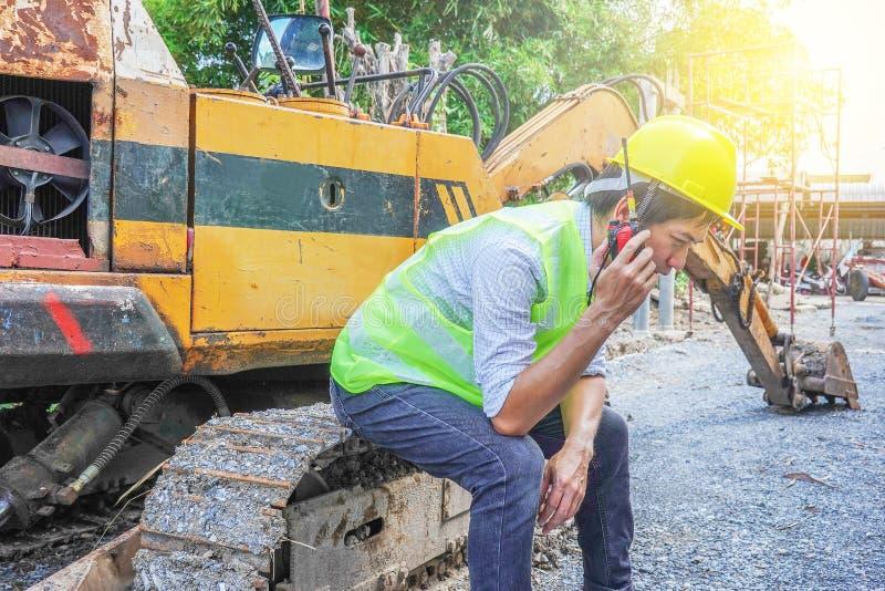 Ritratto di uno sviluppatore maschio che si siede e che parla sul walkie-talkie con un fondo dell'escavatore immagine stock