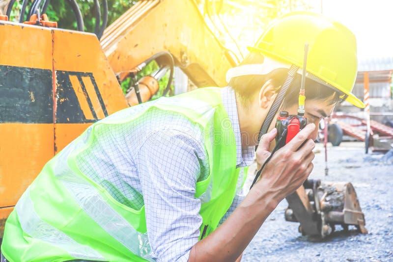 Ritratto di uno sviluppatore maschio che si siede e che parla sul walkie-talkie con un fondo dell'escavatore fotografia stock libera da diritti