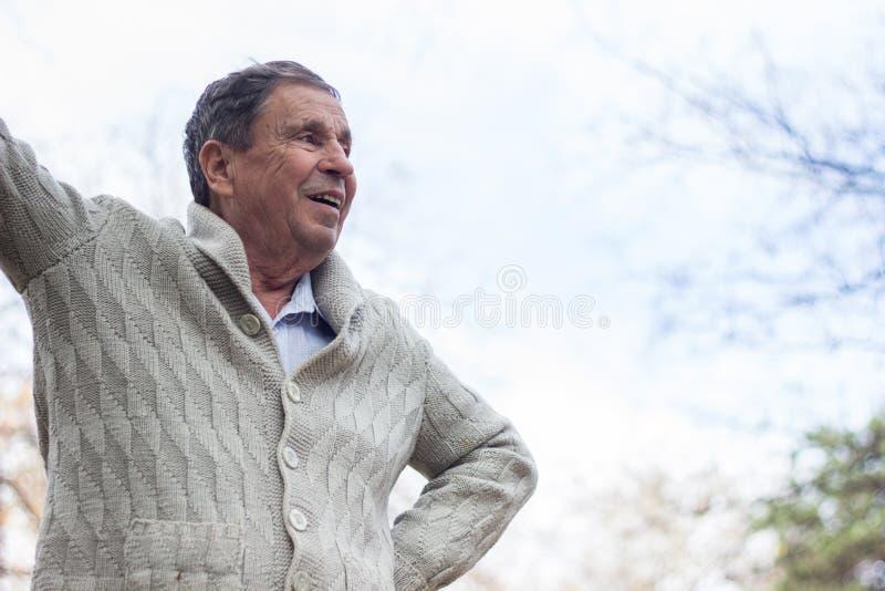 Ritratto di uomo anziano felice che sorride, nel parco pubblico, all'aperto immagine stock