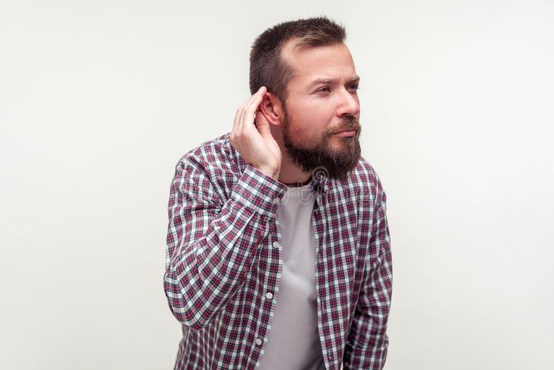 Ritratto di uomo sordo barbuto che sta con la mano vicino all'orecchio e ascolta attentamente le conversazioni segrete fondo bian fotografie stock libere da diritti