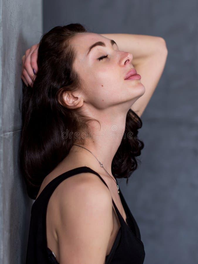 Ritratto di vista laterale di bella giovane donna con capelli marroni che stanno contro la parete con lei piacere chiuso degli oc immagine stock