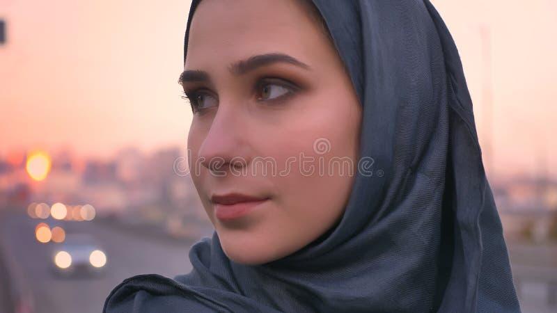 Ritratto di vista laterale del primo piano di giovane fronte femminile attraente nel hijab che guarda in avanti con la città urba fotografie stock libere da diritti
