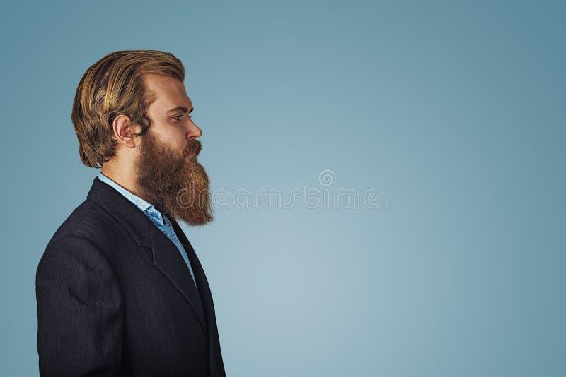 Ritratto di vista laterale dell'uomo barbuto serio in vestito nero, camicia blu fotografia stock
