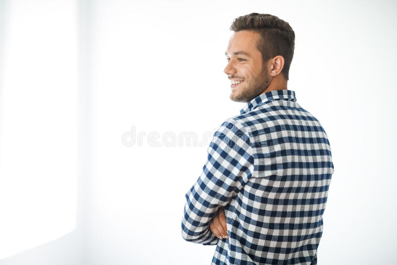 Ritratto di vista laterale dell'uomo bello sorridente su fondo bianco fotografia stock libera da diritti