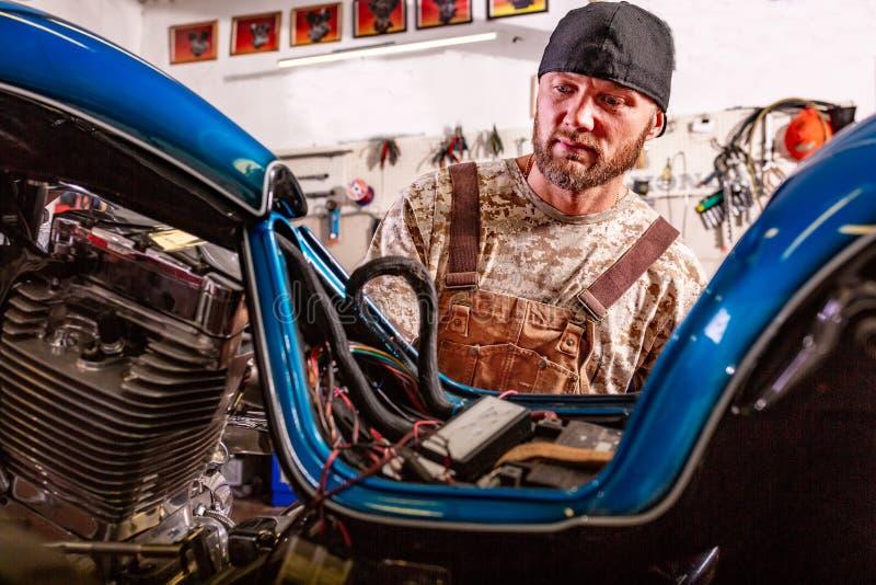 Ritratto di vista laterale dell'uomo che lavora nel garage che ripara motociclo fotografia stock libera da diritti