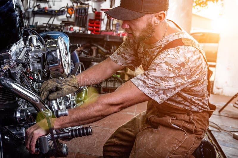 Ritratto di vista laterale dell'uomo che lavora nel garage che ripara motociclo e che lo personalizza immagine stock libera da diritti