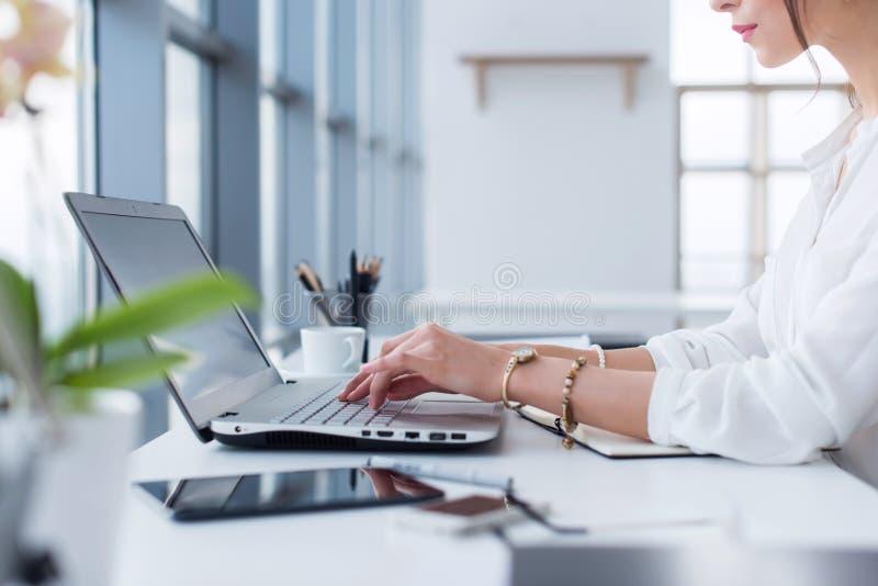 Ritratto di vista laterale della donna che lavora nell'di casa ufficio come Internet di battitura a macchina e praticare il surfi fotografia stock libera da diritti